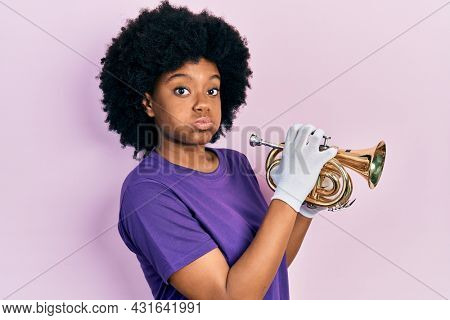 Young african american woman playing trumpet puffing cheeks with funny face. mouth inflated with air, catching air.