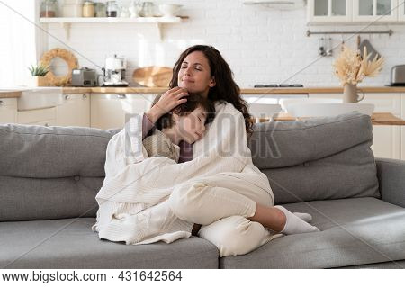 Young Mom Sit On Cozy Couch Relax With Preschool Child Covered With Blanket Bonding With Kid On Week