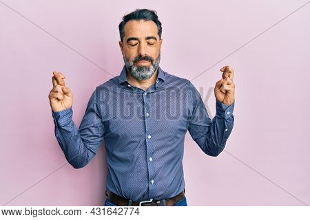 Middle age man with beard and grey hair wearing business clothes gesturing finger crossed smiling with hope and eyes closed. luck and superstitious concept.
