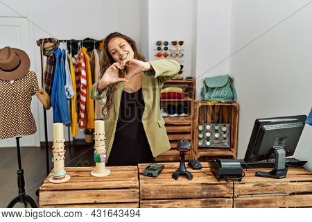 Beautiful hispanic woman working at fashion shop smiling in love doing heart symbol shape with hands. romantic concept.