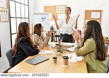Group of young businesswomen smiling and clapping to partner at the office.