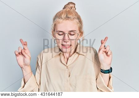 Beautiful caucasian woman with blond hair wearing casual look and glasses gesturing finger crossed smiling with hope and eyes closed. luck and superstitious concept.