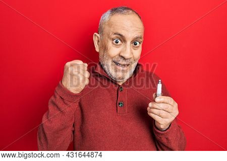 Handsome mature man holding spark plug screaming proud, celebrating victory and success very excited with raised arms