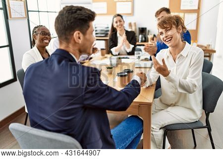 Group of business workers smiling and clapping to partners handshake at the office.