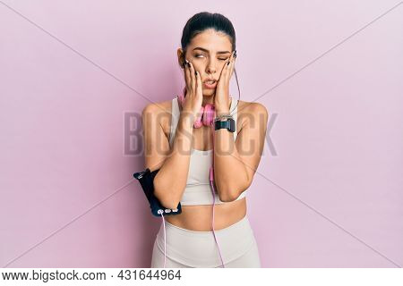 Young hispanic woman wearing gym clothes and using headphones tired hands covering face, depression and sadness, upset and irritated for problem