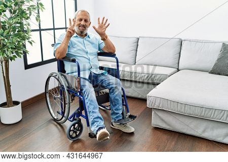 Handsome senior man sitting on wheelchair at the living room showing and pointing up with fingers number seven while smiling confident and happy.
