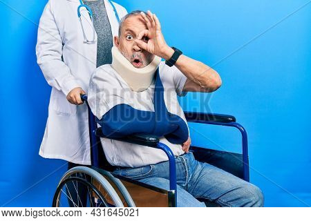 Handsome senior man with beard sitting on wheelchair with neck collar doing ok gesture shocked with surprised face, eye looking through fingers. unbelieving expression.