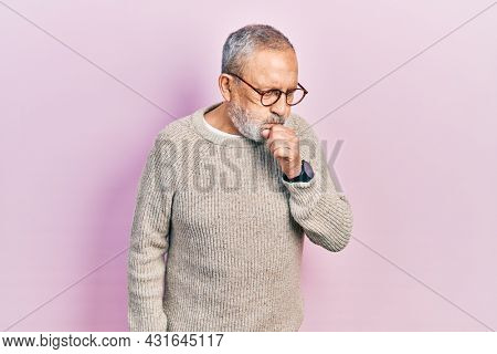 Handsome senior man with beard wearing casual sweater and glasses feeling unwell and coughing as symptom for cold or bronchitis. health care concept.