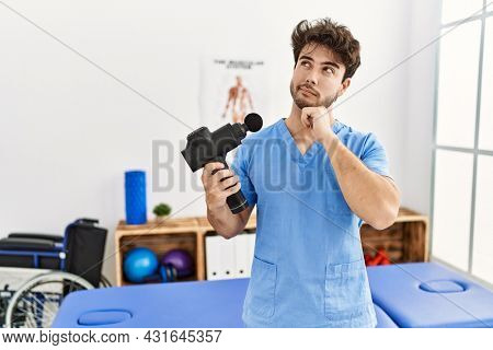 Hispanic physiotherapy man working at pain recovery clinic with muscle gun serious face thinking about question with hand on chin, thoughtful about confusing idea