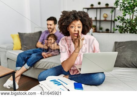 Mother of interracial family working using computer laptop at home hand on mouth telling secret rumor, whispering malicious talk conversation