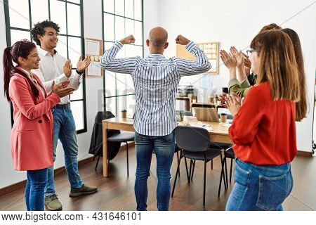 Group of business workers smiling and clapping to partner standing at the office.