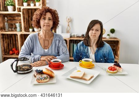 Family of mother and down syndrome daughter sitting at home eating breakfast relaxed with serious expression on face. simple and natural looking at the camera.