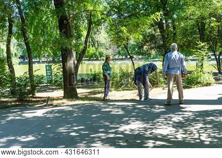 Maintenance Of Public Park And Gardens. Municipal Workers Cleaning Public Park Cismigiu Gardens In B