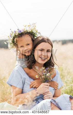 Two Sister Girls Cuddling In A Meadow With Wildflowers