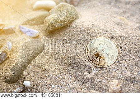 Bitcoin On The Beach Sand With Shells And Stones. Single Golden Btc Crypto Coin Banner In Warm Tones