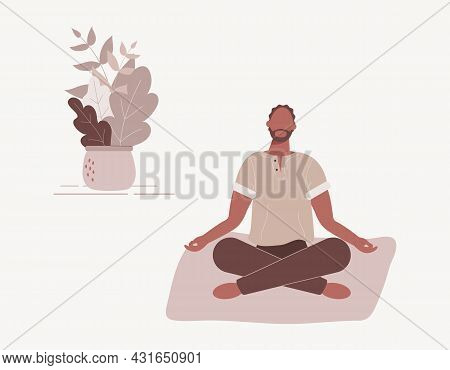 Afro-american Man Sitting With His Legs Crossed On Floor And Meditating. Young Guy In Yoga Posture D
