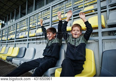 Two Brothers Support Their Favorite Team, Sitting On The Sports Podium At The Stadium.