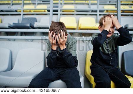 Oh No, They Lost The Game! Two Brothers Support Their Favorite Team, Sitting On The Sports Podium At