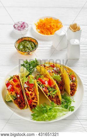 Ground Beef Tacos With Shredded Cheddar Cheese, Green Salsa Verde Sauce, Fresh Lettuce, Tomato, Onio