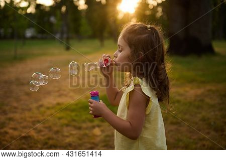 Baby Girl 4 Years Old, Blowing Soap Bubbles Against A City Park Background At Sunset, Enjoying Pleas