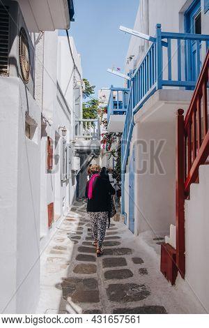 Mykonos Town, Greece - September 23, 2019: People Walking Past Whitewashed Buildings On A Narrow Str