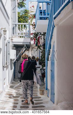 Mykonos Town, Greece - September 23, 2019: Rear View Of People Walking On A Narrow Street In Hora (a