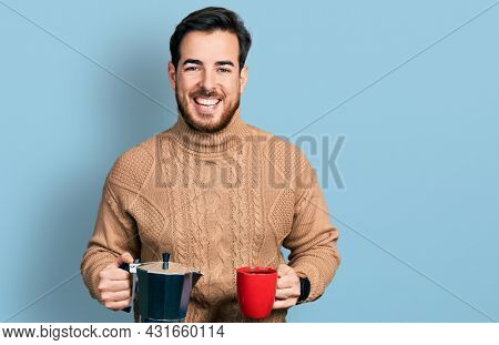 Young hispanic man drinking italian coffee smiling and laughing hard out loud because funny crazy joke.