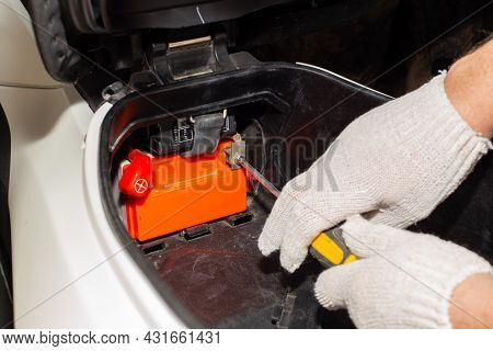A Gloved Auto Mechanic With A Screwdriver Unscrews The Motorcycle Battery Terminals For Repair Or Re