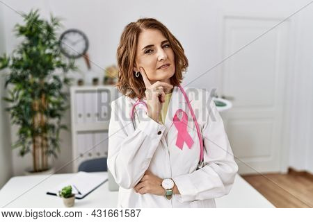 Middle age doctor woman wearing pink cancer ribbon on uniform with hand on chin thinking about question, pensive expression. smiling with thoughtful face. doubt concept.