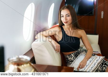 Portrait Of Caucasian Business Woman Passenger On An Airplane, Aboard Private Jet. Young Girl Travel