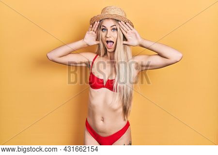 Young caucasian woman wearing bikini and summer hat smiling cheerful playing peek a boo with hands showing face. surprised and exited