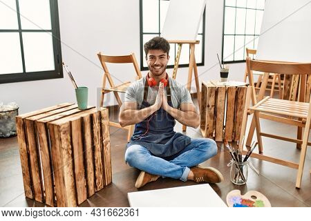 Young hispanic man sitting at art studio praying with hands together asking for forgiveness smiling confident.