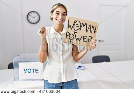 Young blonde woman at political election holding woman power banner screaming proud, celebrating victory and success very excited with raised arm
