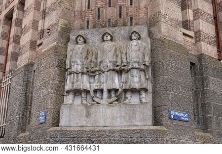 Amsterdam, Netherlands - August 13, 2021: Gray Statue-fresco Of 3 Sailors Holding Anchor At Basse Of