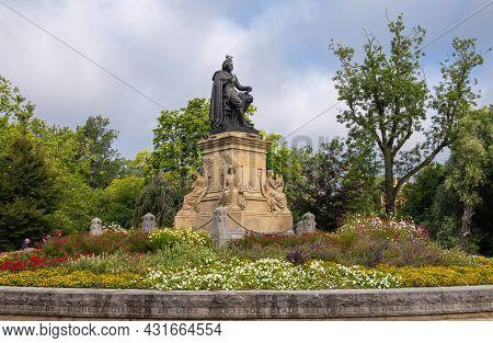 Amsterdam, Netherlands - August 14, 2021: Vondel Bronze Statue On His Beige Sculpted Pedestal Set In