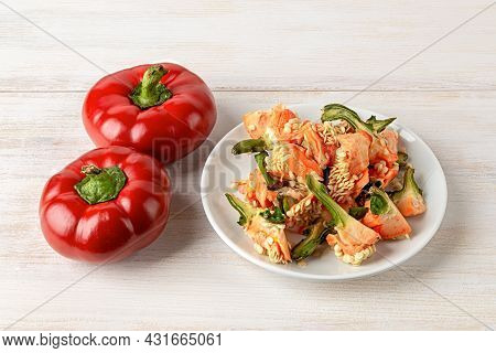 Raw Pepper Peelings On A White Plate And Two Red Ratunda Sweet Peppers Over Kitchen Table. Heap Of O