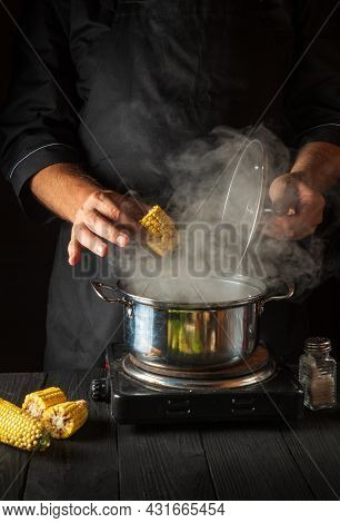 A Professional Chef Cooks Corn. Close-up Of A Cook Is A Hand While Cooking In A Restaurant Kitchen.