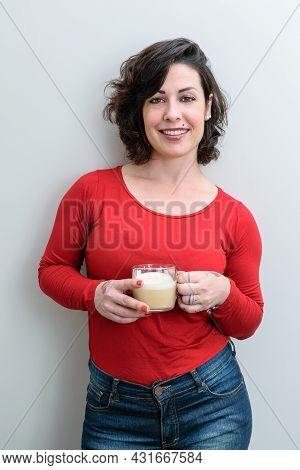 Smiling Brazilian Woman Facing The Camera And Holding A Cup Of Cappuccino (vertical Photo).