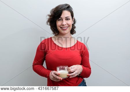 Smiling Brazilian Woman Facing The Camera And Holding A Cup Of Cappuccino.