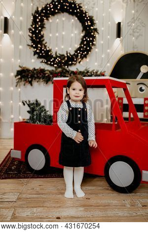 A Little Girl Stands Near A Red Toy Car Against The Background Of A Christmas Wreath Made Of Spruce.