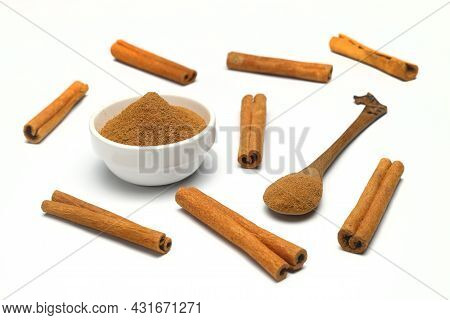 Aromatic Cinnamon Sticks And Bowl With Powder On White Background