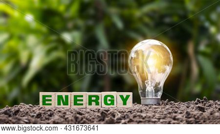 Woodblock Labeled Energy On The Ground And Energy-saving Light Bulbs That Illuminate Green Energy An