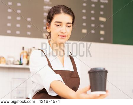 Right Side Of Beautiful Caucasian Barista Woman Shows Takeaway Coffee Cup In One Hand Forward And Lo