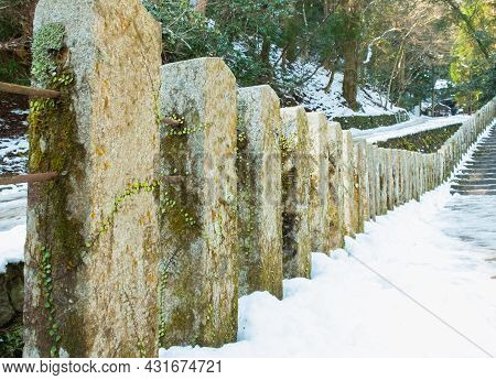 Stone Pillar On Mountain Forest Path With Snow Path In Winter, Pathway With Stone Post In Forest On