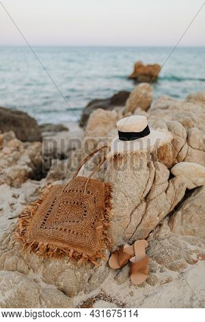 Straw hat and a woven bag on a rocky beach