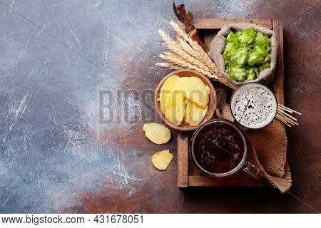 Lager beer mug, bottles, hops and wheat on old stone table. Top view flat lay with copy space