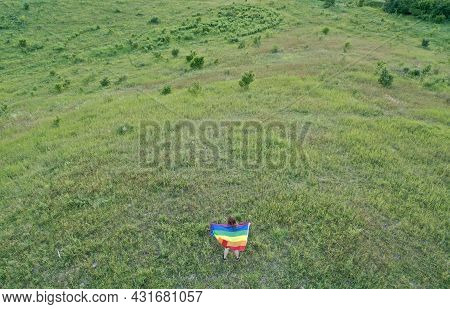 Bisexual, Lesbian, Blonde Woman, Transgender Holds Lgbt Flag On The Green Hills On A Sunny Day And C