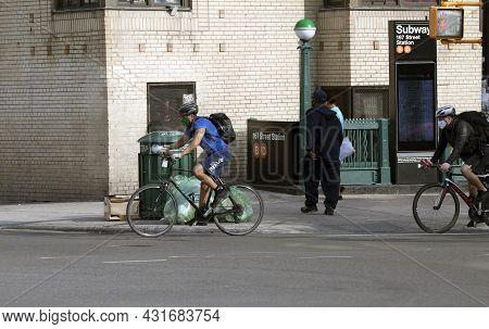 Bronx, New York/usa - May 18, 2020: Men Ride Bikes While Wearing Masks On Local Street.