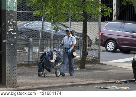 Bronx, New York/usa - May 18, 2020: Postal Worker Pushes Cart Filled With Mail.