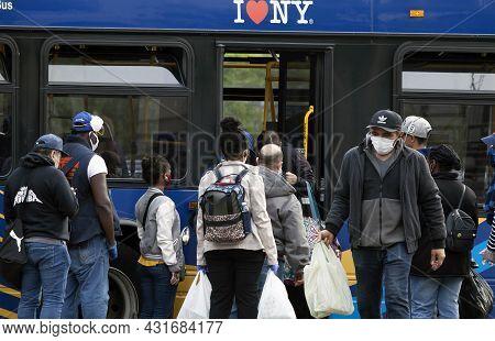 Bronx, New York/usa - May 18, 2020: Group Of People Board Bus Wearing Masks.